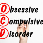 """Photo of the words """"Obsessive Compulsive Disorder"""" written in black ink, with the first letters of each word capitalized, circled, and in red ink. A hand holding a black marker is shown behind the words as if the person holding the marker had written the words.   """"OCD - Obsessive Compulsive Disorder acronym with marker, concept background"""" by Jernej Furman is licensed under CC BY 2.0."""