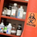 """Photo of a red cabinet containing lab chemicals in labeled plastic and glass bottles. On the right side of the image is a door to the cabinet which is labeled with an orange and black BIOHAZARD sticker.   """"Biohazard chemicals"""" by Wikimedia Commons is licensed under CC BY-SA 4.0."""