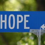 """Photo of a blue street sign which reads, """"HOPE"""" on a background of green tree leaves.   """"Hope"""" by Michael Toy is licensed under CC BY-NC-SA 2.0."""